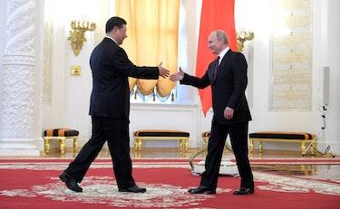 Xi Jinping og Vladimir Putin håndhilser.